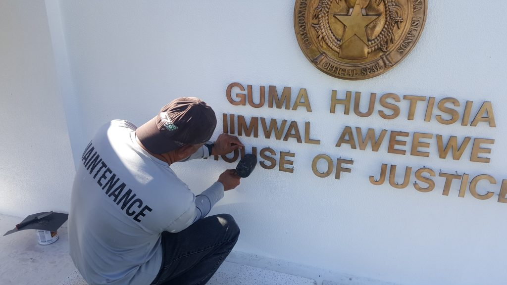 Ray Babauta polishing the sign of the House of Justice